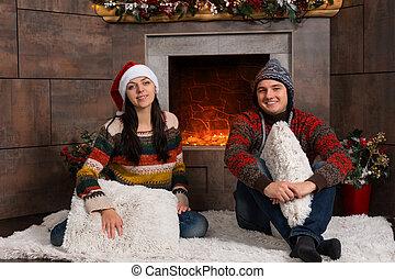 dekorerat, par, vinter, le, sittande, ung, rolig, främre del, matta, eldstad, hattar