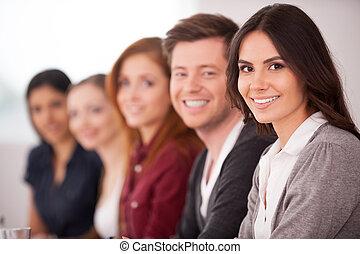 kvinna, henne, sittande, kamera, folk, ung, seminar., medan, annat, attraktiv, bak, le, rad