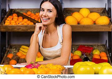 kvinna räcka, kärlek, förkläde, frukter, job!, ung, min, bakgrund, ombyte, specerier, leende stå, lager, hand, haka, vacker, medan