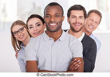 stående, se, hålla, team., grupp, affärsfolk, vapen, ung, glad, tillitsfull, bak, kamera, medan, afrikansk, korsat, leende herre, honom, rad