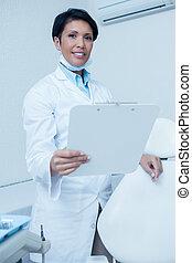 tandläkare, kvinnlig, holdingen, le, skrivplatta