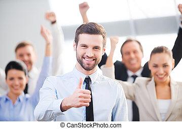 tillitsfull, känsla, affärsman, uppe, lycklig, bakgrund, tumme, team., visande, leende stå, hans, kolleger, medan