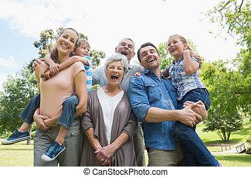 vidgad, parkera, stående, glad, familj